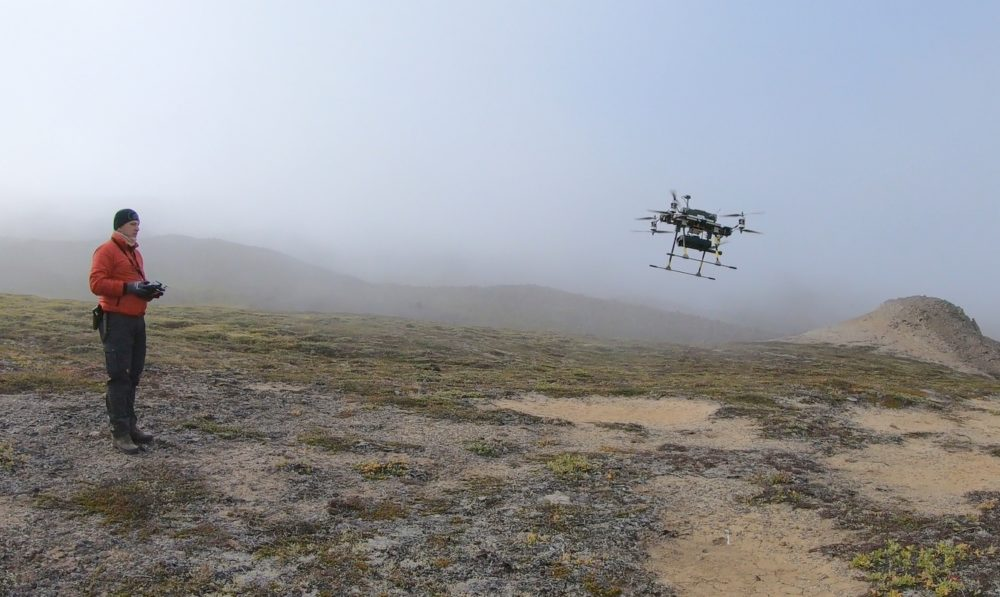 Figure 1. HZDR-HIF's multi-copter Tholeg THO-R-8/10 equipped with a Sensys MagDrone R1 magnetometer. Robert Zimmerman (HZDR-HIF) is controlling the landing during field operations in Greenland in 2019 (Photo: Heikki Salmirinne, GTK).