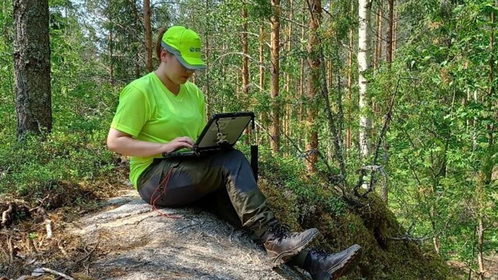 Kesäharjoitelija Venla Vehanen tallentaa havaintoja kalliolla istuen.