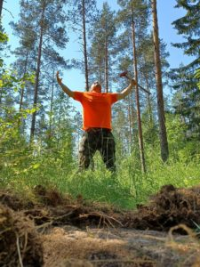 Man in an orange shirt spreads arms in forest